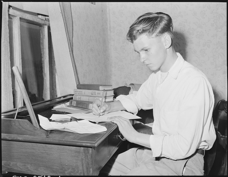 Louis Sergent, 16, who is in his first year at high school, does his homework. Both he and his father are determined that he will finish high school and not work in the coal mines. With the exception of Lucy who is blind and attended the State School for The Blind, Louis is the first member of the family to finish grade school. P V & K Coal Company, Clover Gap Mine, Lejunior, Harlan County, Kentucky. Date 13 September 1946. Russell Lee (Public domain), via Wikimedia Commons