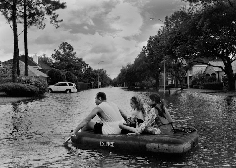 A family in Katy, just west of Houston, floats on an inflatable mattress. PHOTOGRAPHER: PHILIP MONTGOMERY FOR BLOOMBERG BUSINESSWEEK